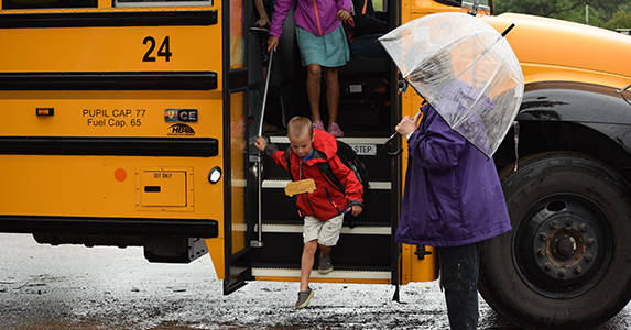 Boys steps off a school bus