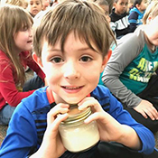 Boy holding small jar of butter