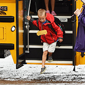 Boy hops off the bus for his first day of school