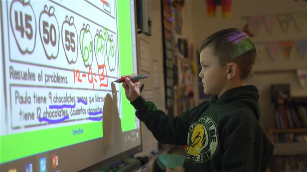 Boy working at Smart Board in school classroom