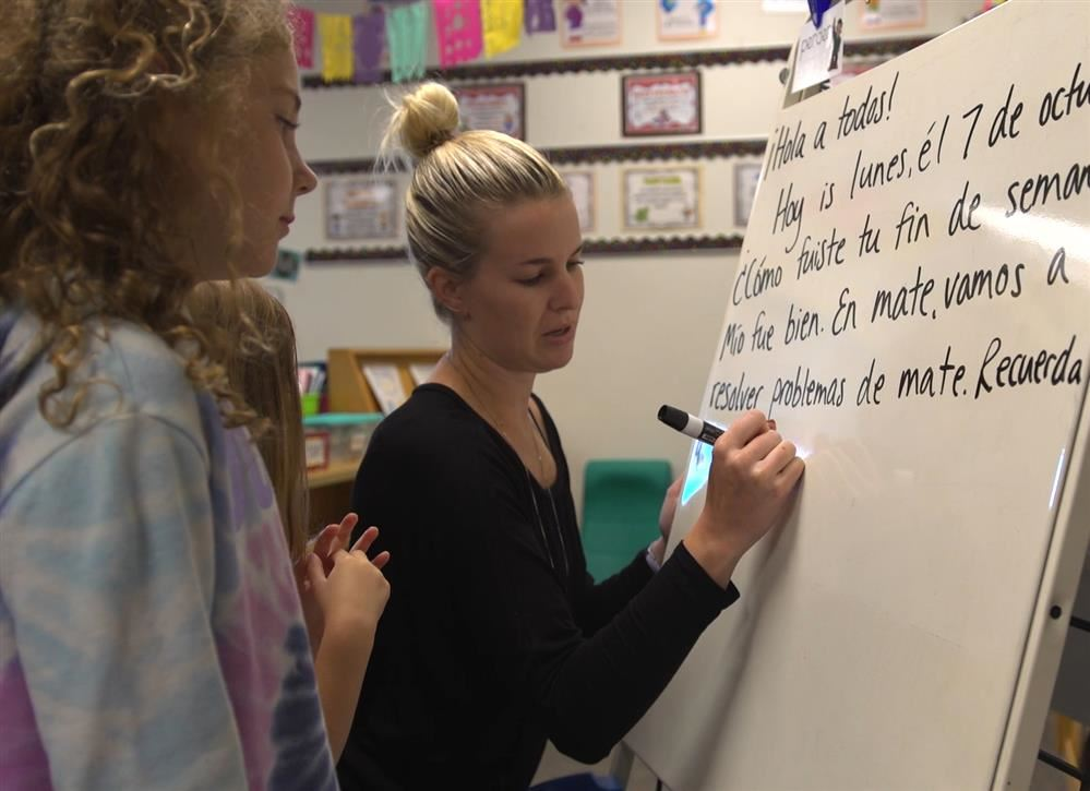 Teacher writes in Spanish on a white board while student looks on