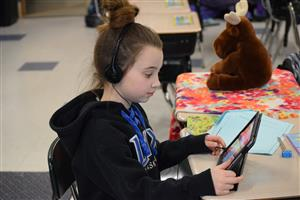 Girl sits at a desk reading from an iPad