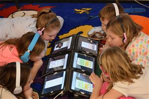 Six students lie with heads together, reading from iPad screens