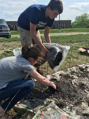 Two high school students plant a rain garden on high school property