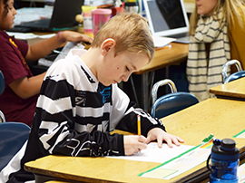 Boy works at his desk in a classroom, filling out a worksheet with a pencil