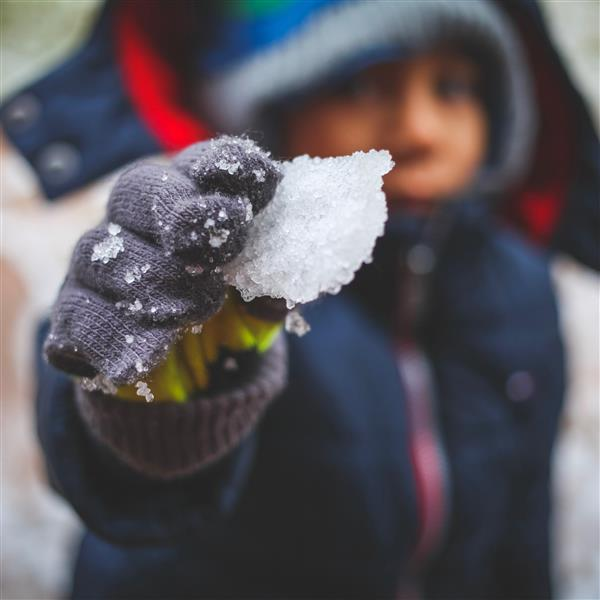 A piece of snow is held up by a child in winter gear