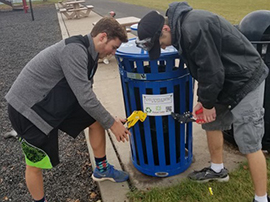 Two high school boys rivet a sign onto a recycling bin in a park