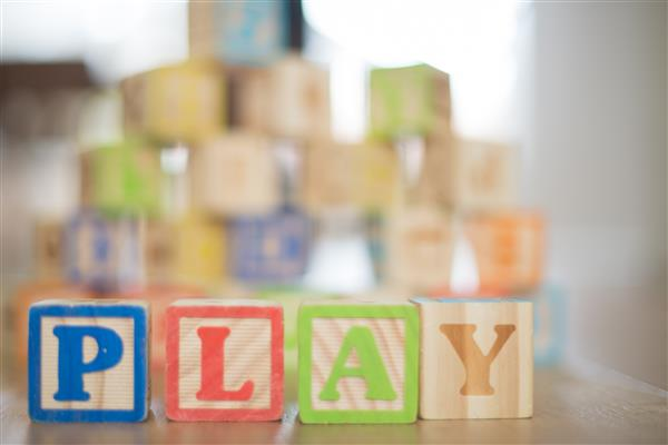 Letter blocks spelling the word play.