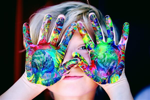Boy with paint on hands, peeking through fingers.